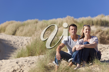 A romantic young man and woman couple sitting together in the sand dunes of a sunny beach with a bright blue sky