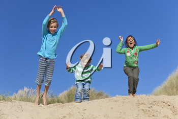 Three children, two blond boys and a mixed race little girl, having fun arms raised and jumping in the dunes of a sandy beach
