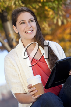 A happy young woman or girl student drinking coffee and using an tablet computer