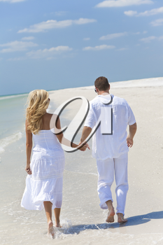 Happy young man and woman couple running or walking and holding hands on a deserted tropical beach with bright clear blue sky