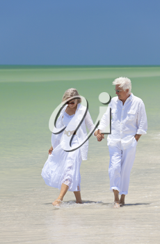 Happy senior man and woman couple walking, smiling and holding hands on a deserted tropical beach with bright clear blue sky