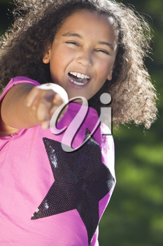 Portrait of a beautiful young happy mixed race interracial African American girl pointing, shot outside in summer sunshine