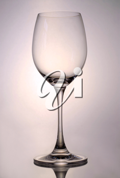 Single empty glass for white wine on reflective surface