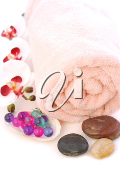 Pink rolled up towel with massage stones and bath beads on white background