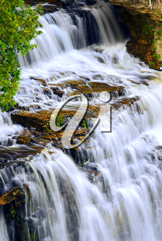 Beautiful cascading waterfall flowring over natural rock formation