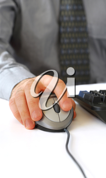 Closeup of man's hands with computer mouse and keyboard