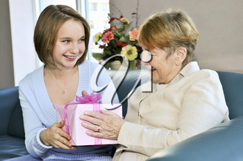 Granddaughter bringing wrapped gift to her grandmother