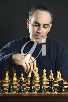 Man moving a chess piece on wooden chessboard