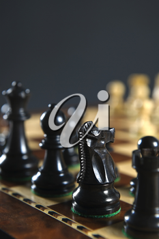 Close up of black chess pieces on wooden chessboard