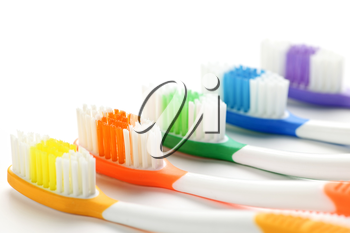 Close up of multicolored toothbrushes on white background