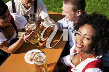 Group of four people - two Couples - in traditional Bavarian dress, Lederhosen and Dirndl, in a beer garden with Pretzel and Obatzter (traditional cheese)