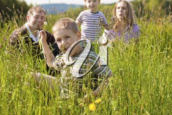 Very happy family with two kids sitting in a� meadow in the summer sun in front of a forest and hills, they are nearly hidden by the high grass, on boy is running towards the viewer