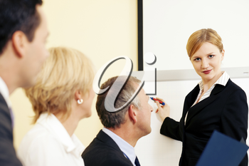 Business team receiving a presentation held by a female co-worker standing in front of a flipchart