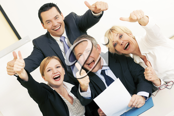 Business people having a lot of fun and letting it show by doing the thumbs up sign, celebrating a success