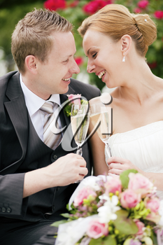 Newlywed couple - bride and groom - clinking glasses with champagne after their wedding