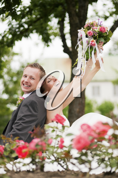 Visibly happy newlywed couple sitting in a park with a lot of roses in foreground