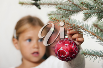 Young girl helping her father decorating the Christmas tree, holding some Christmas baubles in her hand (Focus on bauble!)