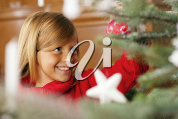 Young girl helping decorating the Christmas tree, holding some Christmas baubles in her hand (Focus on girl)