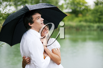 Couple (man and woman) at a lake in summer rain with an umbrella, he is sheltering her from the drops, holding his girl in his arms
