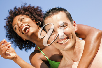 Couple in love - bikini-clad woman of color hugs a Caucasian man from behind under clear blue sky, both in beachwear in summer
