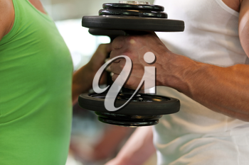 Couple exercising with dumbbells in a gym, focus on hands