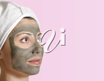 Female face with a clay mask and with space for your message.