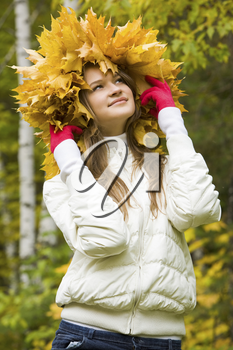 Portrait of smiling young woman wearing wreath of maple leaves