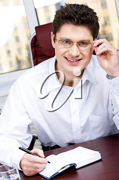 Portrait of smiling boss touching his glasses holding a pen and sitting at the table