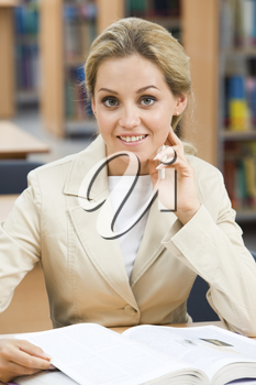 Portrait of smart lady sitting in library with open encyclopedia near by and looking at camera with smile