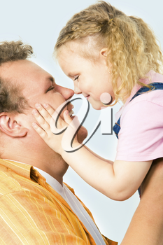 Close-up of happy man holding his daughter over white background