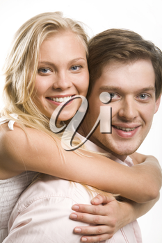 Image of happy couple looking at camera with smiles while pretty blonde embracing her boyfriend