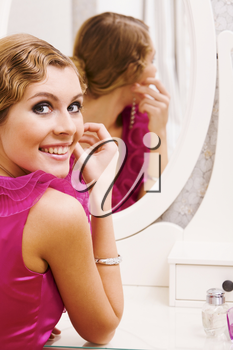 Image of pretty female looking at camera while putting on earrings