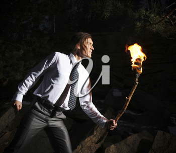 Image of brave man with burning stick while moving in darkness