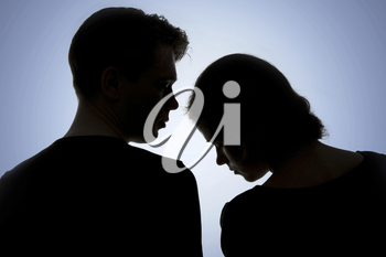 Two heads of amorous people close to each other on blue background