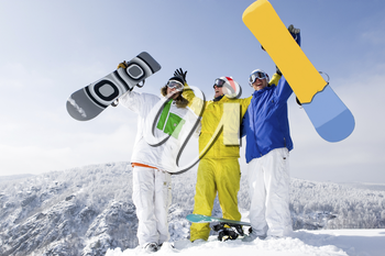 Portrait of three successful snowboarders raising their arms on mountain top