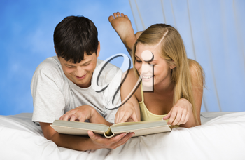 Portrait of man and woman reading the book together in the bed