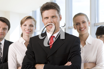Several business partners looking at camera with successful man in front
