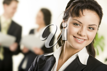 Face of happy businesswoman on background of working partners in office