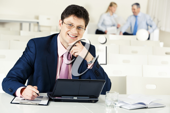 Photo of confident businessman working at laptop on the background of his partners
