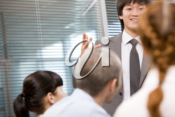 Photo of several employees during presentation with focus on their leader