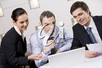 Portrait of executive employees looking at laptop monitor with pensive boss between them and discussing new project