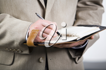 Photo of businessman holding the pen and notepad