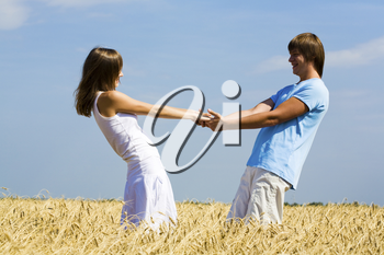 Image of happy young man and woman holding each other by stretched hands while standing on wheat field