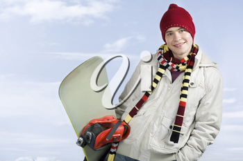 Portrait of healthy young male wearing sporty clothes holding snowboard and looking at camera with smile