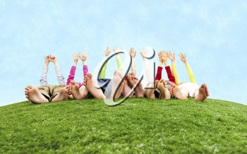 Image of several children lying on the grass and stretching their hands to the sun