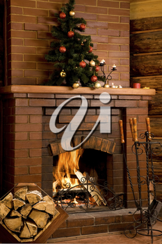 Image of chimney with fire inside and decorated tree on its top