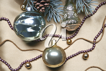Christmas composition: glassy balls, beads and part of a Christmas twig with fir cone