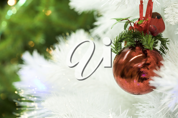 Close-up of red toy ball hanging on white fluffy branch of artificial fir tree