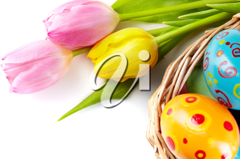 Composition of tulip bouquet with basket of Easter eggs near by