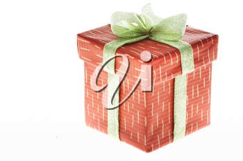 Isolated gift in decorative box bound with golden ribbon and bow on its top